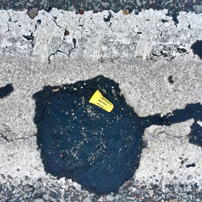 wire cap embedded in road tar
