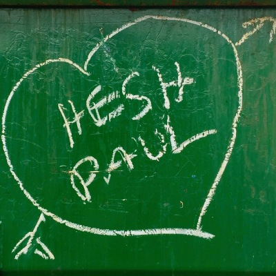 "graffiti written on green dumpster with the names ""Hesh"" and ""Paul"" in a white heart"