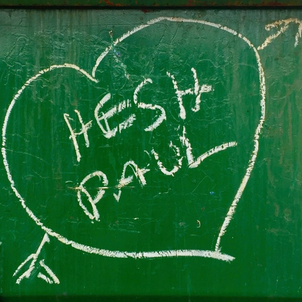 """graffiti written on green dumpster with the names """"Hesh"""" and """"Paul"""" in a white heart"""