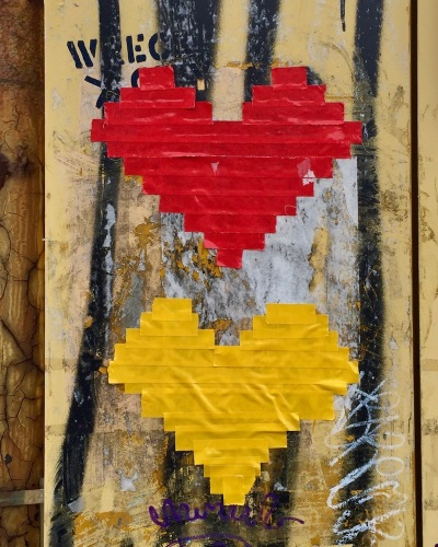 heart images made from red and yellow tape on electrical box