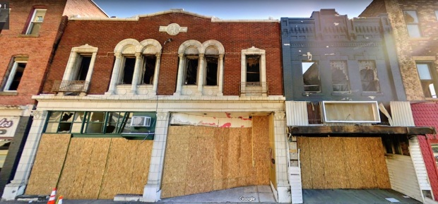 two brick retail buildings in downtown New Kensington, PA with second floor windows removed and plywood covering the storefronts