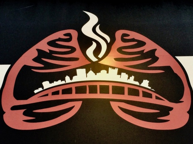 logo for Iron Lung vape shop that features the Pittsburgh skyline inside a pair of red lungs