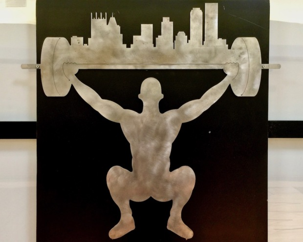 metal logo for Legends of Pittsburgh gym with weightlifter holding barbell with the city of Pittsburgh skyline on it