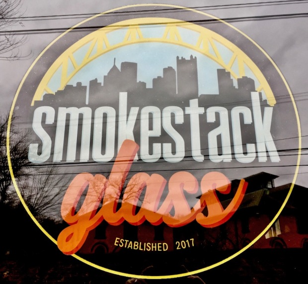 window sign for Smokestack Glass including the Pittsburgh skyline