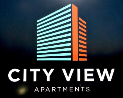 signage for City View Apartments featuring simplified graphic version of the building's shape