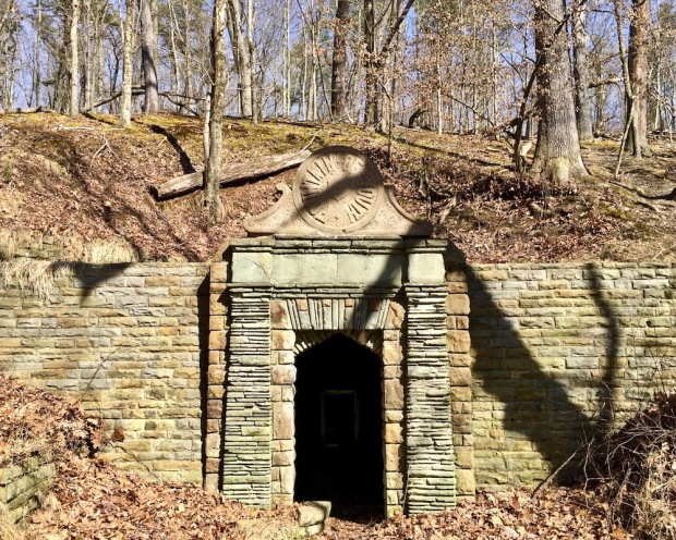 entrance to spring house grotto built into wooded hillside