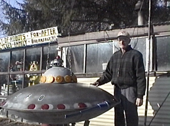 artist DeVon Smith with sculpture of UFO in front of his home in Wampum, PA, 2001
