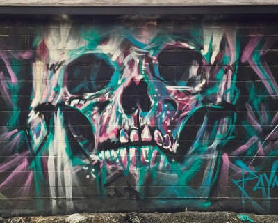 mural of multicolor skull by artist Jeremy Raymer