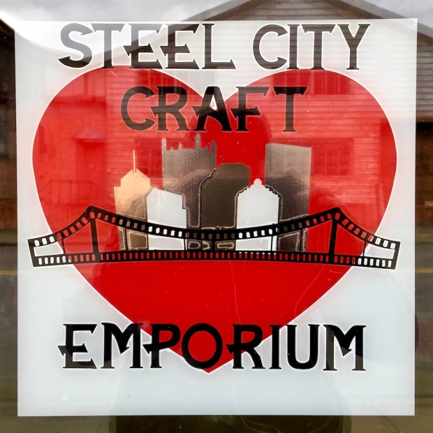 window sign for Steel City Craft Emporium featuring downtown Pittsburgh skyline