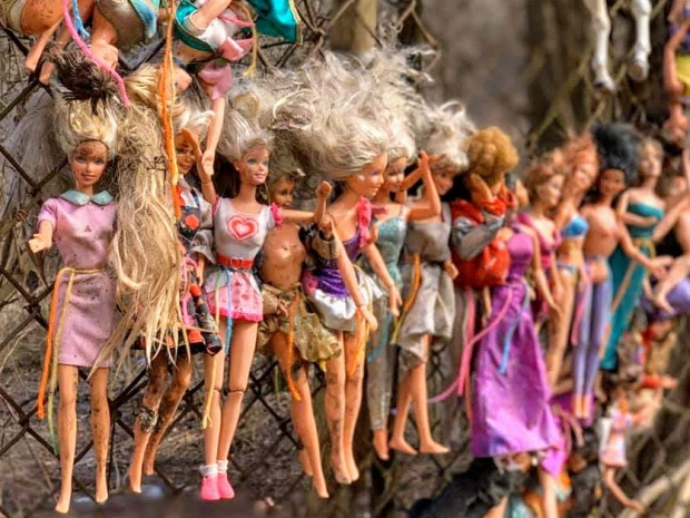 collection of Barbie dolls attached to chain link fence