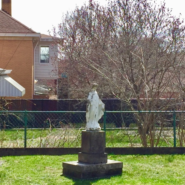 statue of Mary on pedestal in residential backyard
