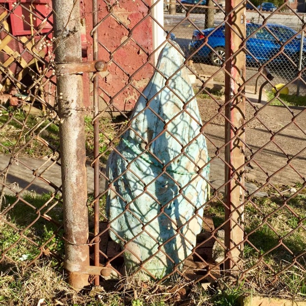 rear-view statue of Mary behind chain link fence