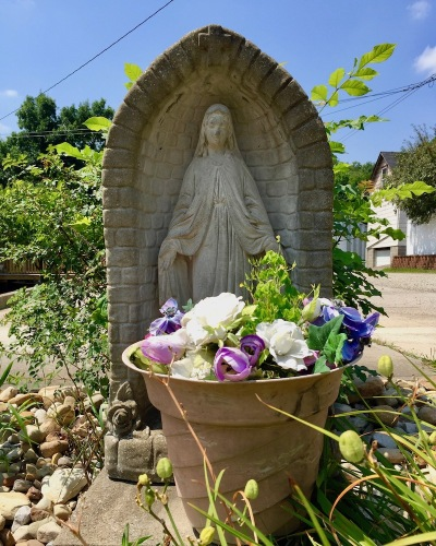 statue of Mary and flowers in pot