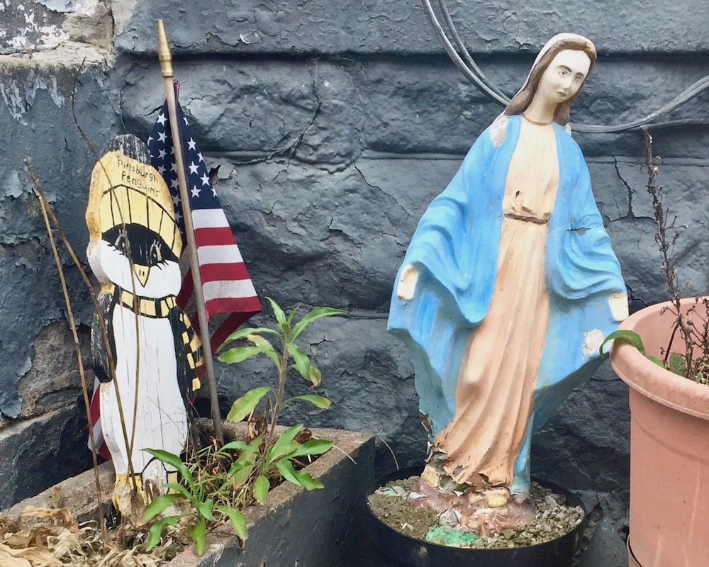 statue of Mary embedded in concrete in flower pot