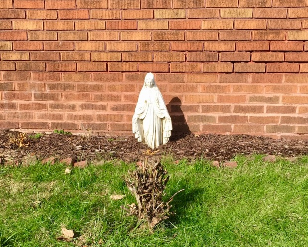 statue of Mary with feet buried in garden mulch