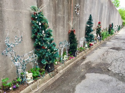 concrete retaining wall decorated with artificial Christmas trees, flowers, and other items