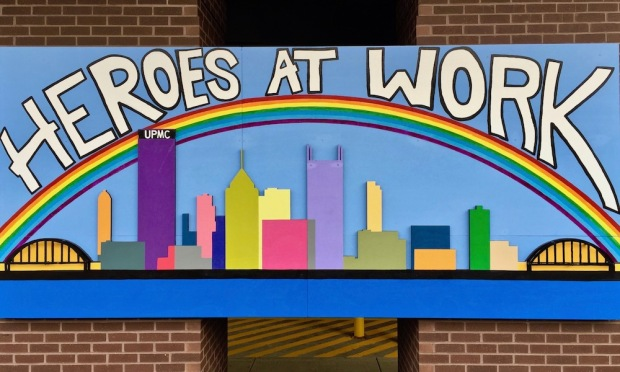 "hand made multicolor sign reading ""Heroes at Work"" over rainbow over downtown Pittsburgh skyline"