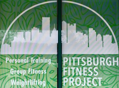 printed sign for Pittsburgh Fitness Project gym including image of the downtown skyline