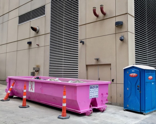 pink breast cancer awareness dumpster behind large building