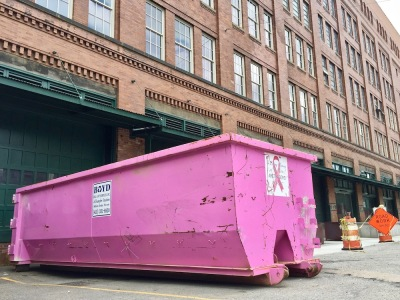 dumpster painted bright pink in front of large brick building
