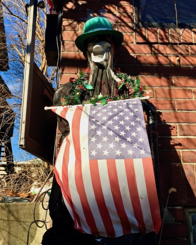 skeleton decorated with green hat, Christmas garland, and American flag