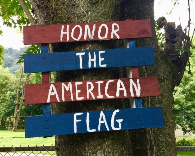 "handmade sign reading ""Honor the American flag"""