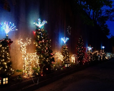 row of Christmas decorations against retaining wall in long alley