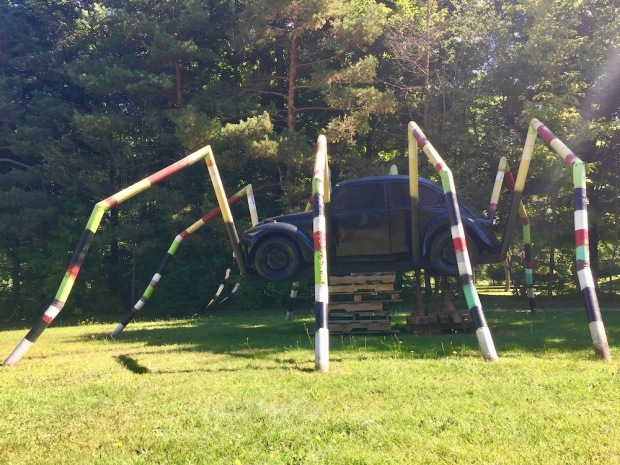sculpture of giant multicolor spider with Volkswagen Beetle as the body
