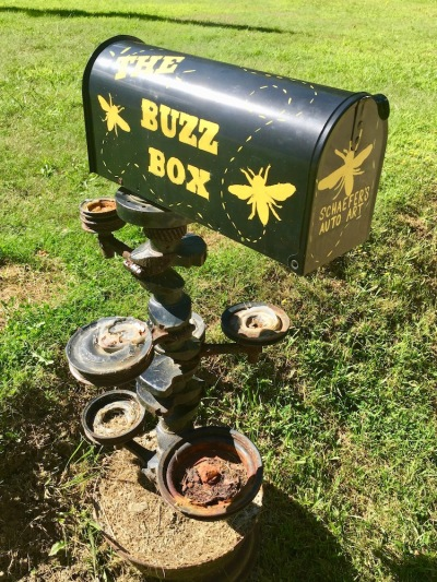 "mailbox painted with insects and the words ""The Buzz Box"""