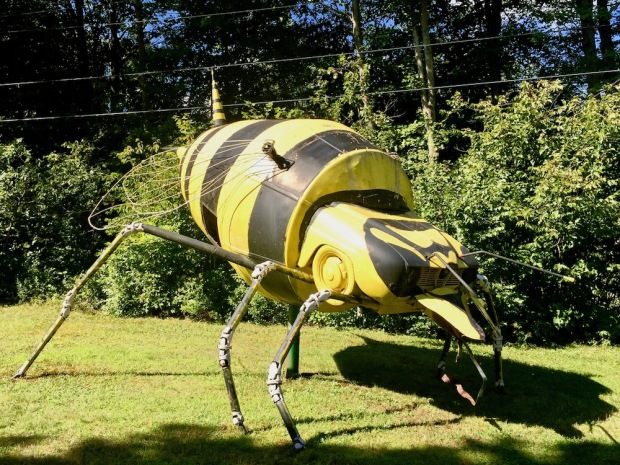 large outdoor sculpture of yellow and black flying insect made with recycled parts