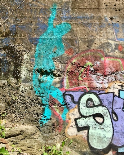 layers of graffiti on cement wall