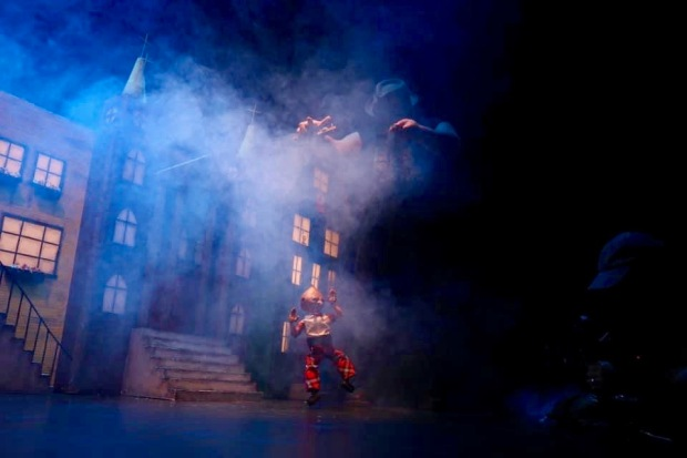 puppeteer with marionette on stage set including city buildings and smoke