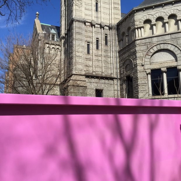 pink breast cancer awareness dumpster in front of old stone building
