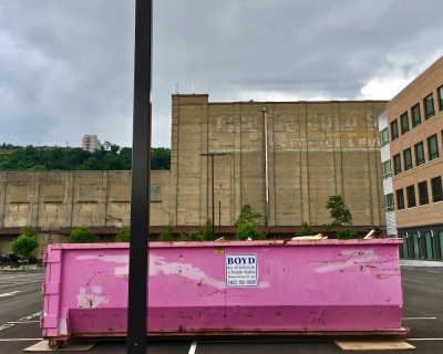pink breast cancer awareness dumpster in large parking lot