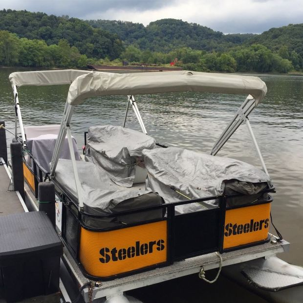 pontoon boat decorated with for the Pittsburgh Steelers docked in river