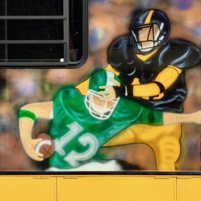 airbrush painting of football players on side of large RV