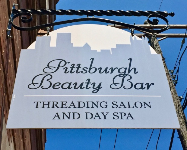shop sign for Pittsburgh Beauty Bar including silhouette of the city skyline