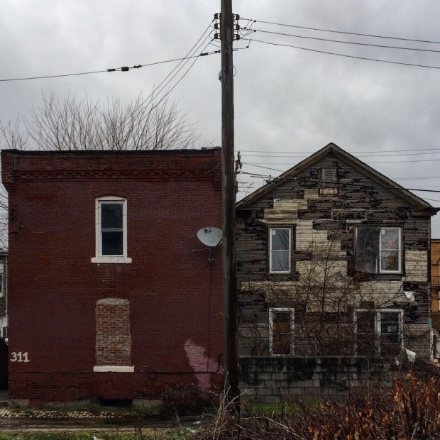 brick row house with flat roof next to wooden row house with peaked roof, McKees Rocks, PA