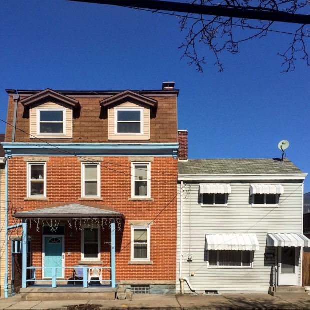 large brick row house next to small row house with aluminum siding, Pittsburgh, PA