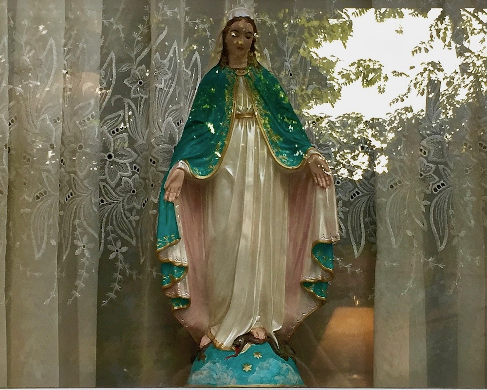 statue of Mary in front window of house