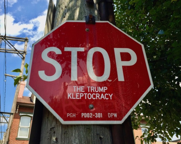 """stop sign with added sticker to read """"Stop the Trump kleptocracy"""""""