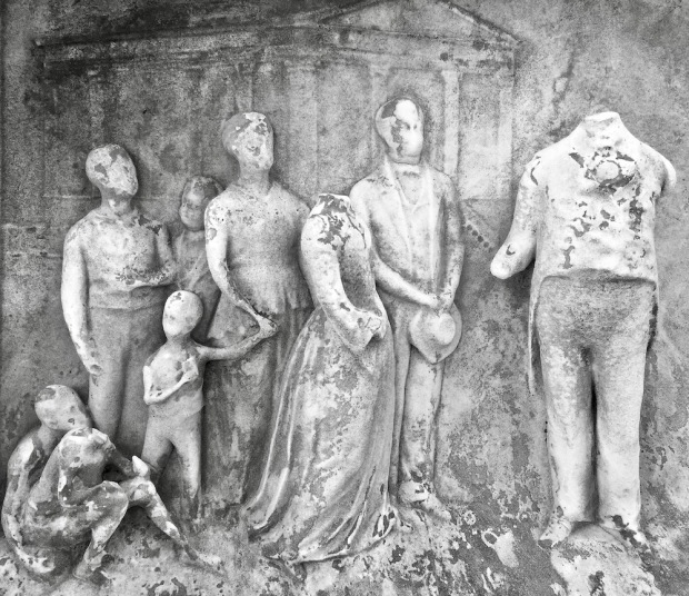 detail from marble cemetery monument of carved family whose features have eroded
