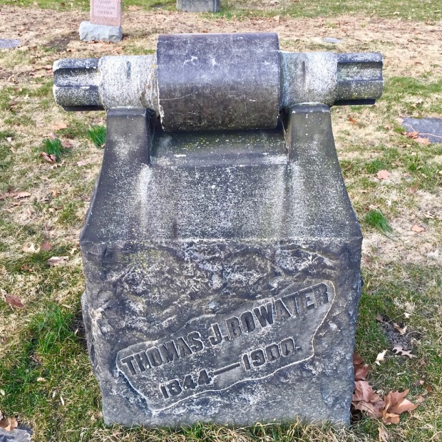 stone grave marker featuring large spinning machine part