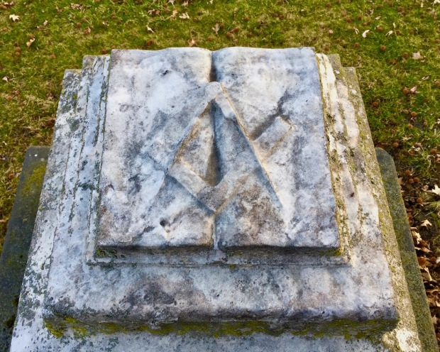 stone memorial featuring a book with the Freemason's square and compass symbol