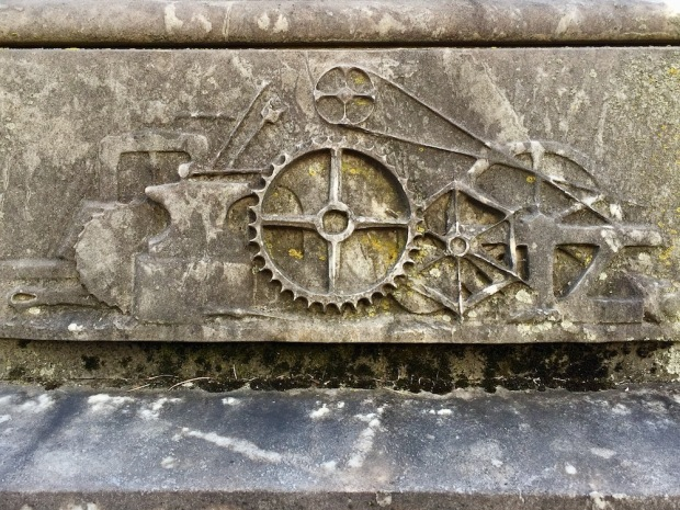 detail from cemetery monument featuring chiseled gears/machine imagery