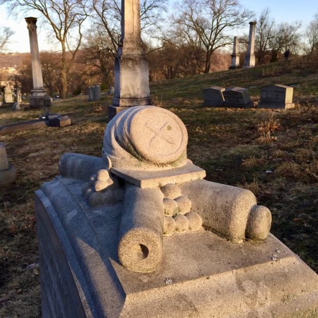 detail from Civil War soldier's gravestone featuring hat, cannons, and cannonballs