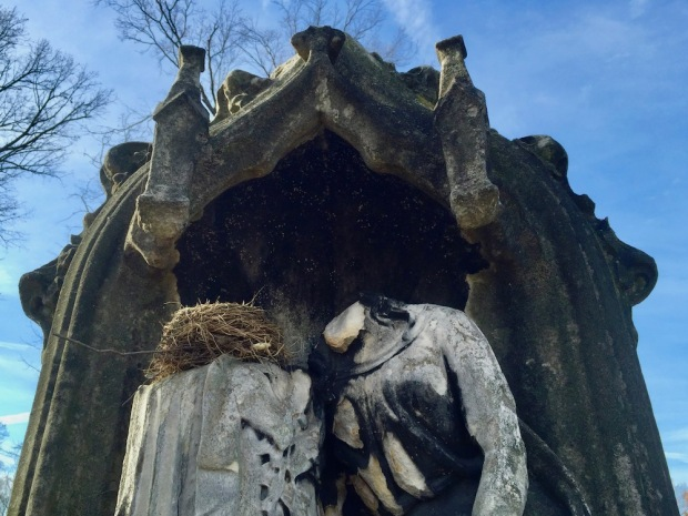 intricate stone cemetery memorial including a female figure missing her head and a real bird's nest