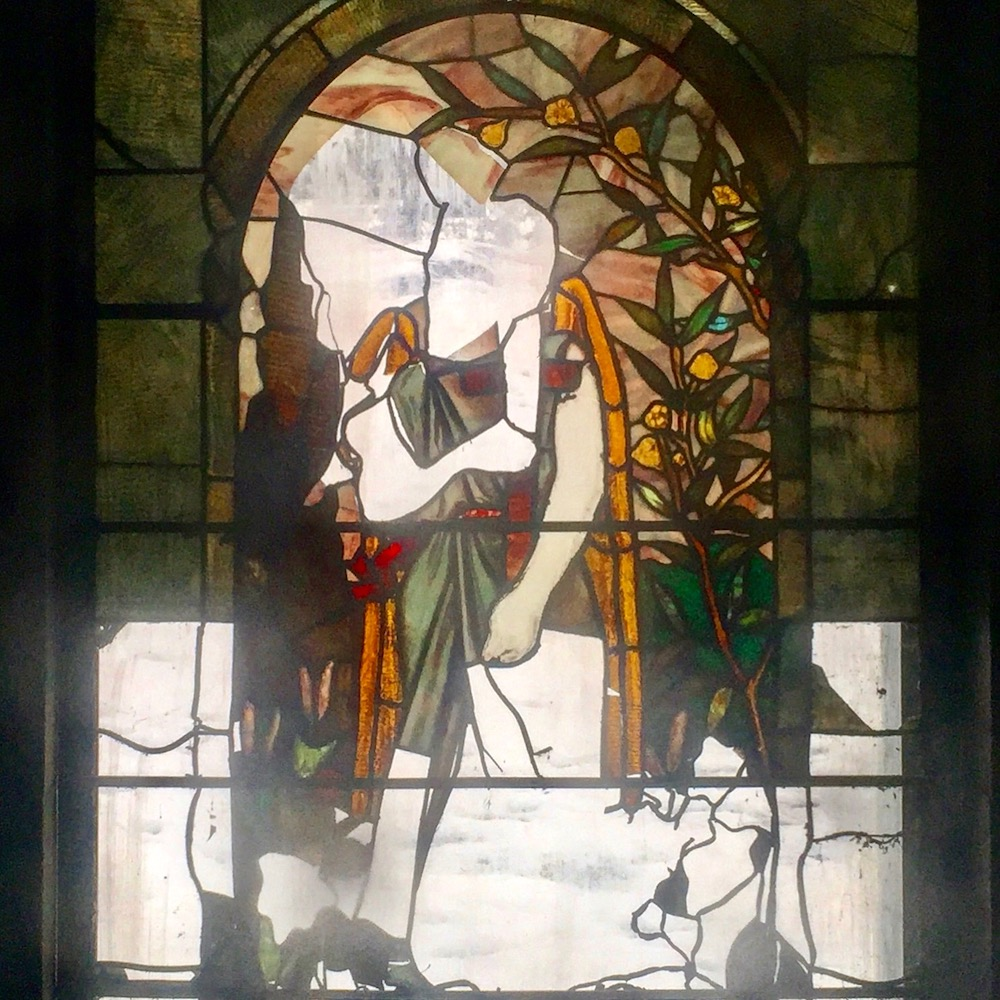 stained glass window of figure in garden with many glass panes missing