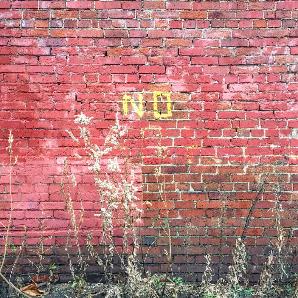 "brick wall with word ""No"" painted on it"
