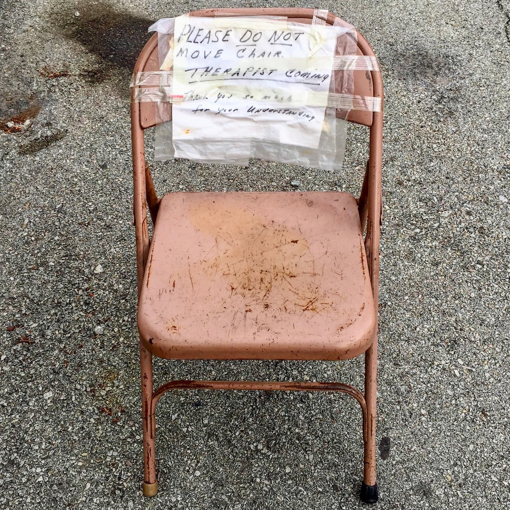 "metal folding chair with hand-written sign reading ""Please do not move chair. Therapist coming."""
